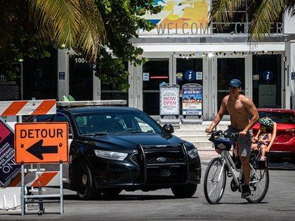 Un hombre y un niño fueron registrados este viernes al recorrer, en bicicleta y sin protección facial, el paseo turístico de Ocean Drive, en Miami Beach (Florida, EE.UU.). EFE/Giorgio Viera