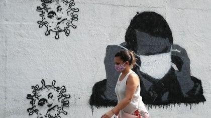 Foto de archivo. Una mujer pasa por delante de un grafiti que muestra al presidente de Brasil, Jair Bolsonaro, ajustando su máscara protectora, en medio del brote de la enfermedad coronavirus (COVID-19) en Río de Janeiro, Brasil. 2 de julio de 2020. REUTERS/Sergio Moraes