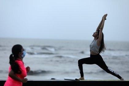 Una mujer practica yoga en la costa de Mumbai