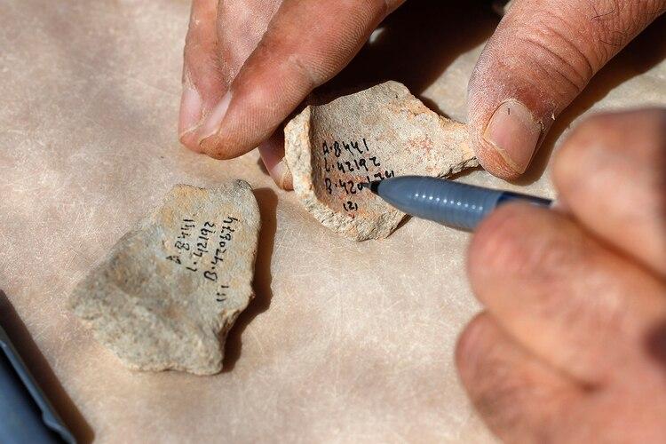 Un trabajador marca números de referencia en fragmentos de cerámica desenterrados en el sitio arqueológico (Jack Guez/ AFP)