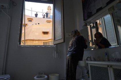 Turistas en el techo del edificio viendo hacia el baño de Viladomiu (Samuel Aranda para The New York Times)