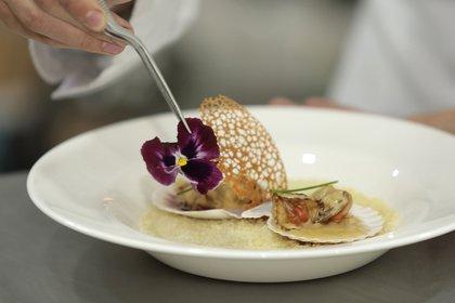 Vieiras con salsa de vino blanco, touille de pimentón ahumado, sal con colorante y la decoración con flor del pensamiento (comestible).