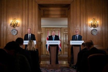 El Director Médico de Reino Unido, el Profesor Chris Whitty (izquierda) y el Asesor Científico Jefe Patrick Vallance miran al Primer Ministro Británico Boris Johnson durante la conferencia de prensa  (Leon Neal/Pool vía REUTERS)
