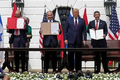 El ministro de Relaciones Exteriores de Baréin, Abdullatif Al Zayani; el primer ministro de Israel, Benjamin Netanyahu, y el ministro de Relaciones Exteriores de los Emiratos Árabes Unidos (EAU), Abdullah bin Zayed, exhiben sus copias de los acuerdos firmados, junto al presidente de los Estados Unidos, Donald Trump, en el jardín sur de la Casa Blanca en Washington, Estados Unidos. 15 de septiembre de 2020. REUTERS/Tom Brenner