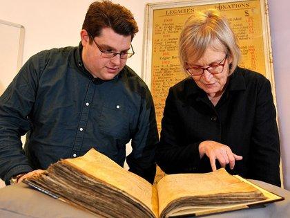 Los investigadores Sarah Rees Jonesy Gary Brannan observan los registros del arzobispo William Melton (University of York)