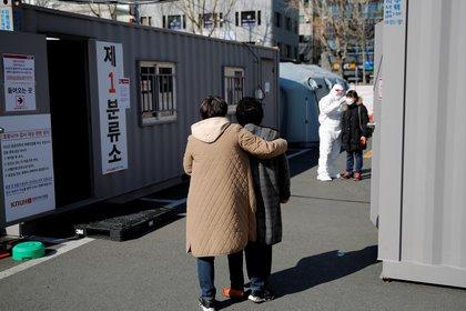 Una mujer con su hija espera su turno para que le tomen la temperatura en el puesto de control de la primera etapa para comprobar la enfermedad coronavirus (COVID-19) en el Hospital Universitario Nacional de Kyungpook en Daegu, el 6 de marzo de 2020 (Reuters/ Kim Kyung-Hoon)