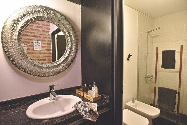 El baño original del loft, con un antebaño donde se ubica la mesada de granito negro con la bacha embutida, remata en un espejo ovalado con marco calado, comprado en un viaje. Una puerta corrediza lo separa del baño principal, que acomoda al fondo el box de ducha con mampara de vidrio y escalera de diseño como toallero. Foto Gustavo Bosco/ Para Ti