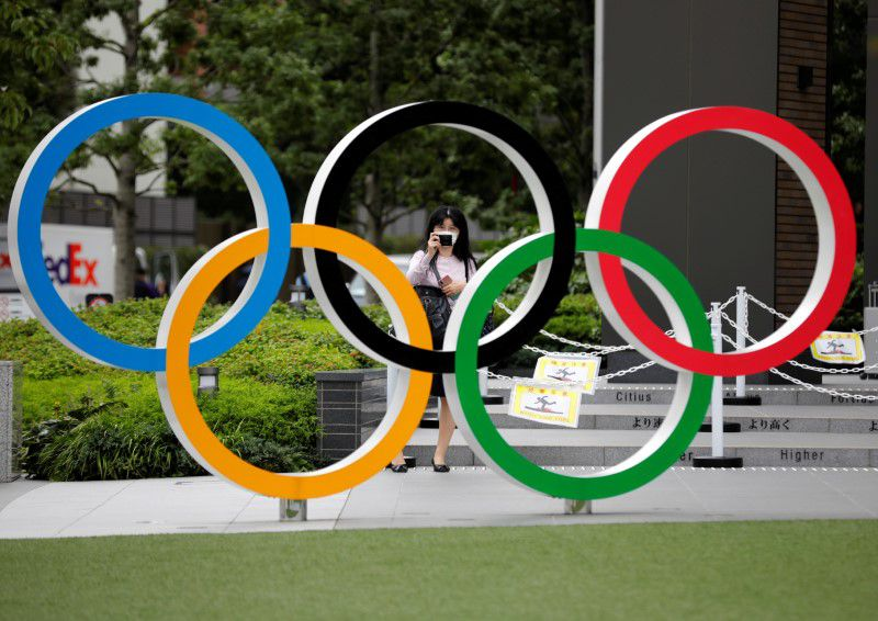IMAGEN DE ARCHIVO. Una mujer utilizando mascarilla toma una fotografía a os anillos olímpicos frente al Estadio Nacional de Tokio, Japón October 14, 2020. REUTERS/Kim Kyung-Hoon
