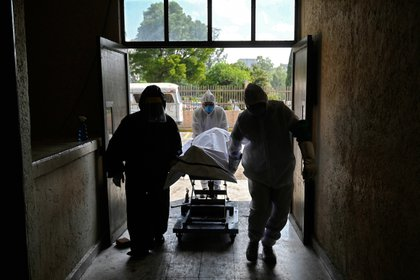 Trabajadores forenses transportan el cuerpo de una persona que falleció por COVID-19 al panteón de San Isidro, Azcapotzalco Foto: (ALFREDO ESTRELLA / AFP)