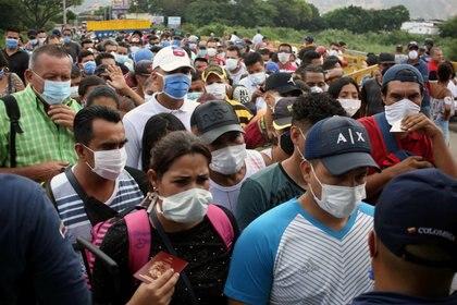 Venezolanos cruzando la frontera hacia Colombia, usando mascarilla para prevenir el coronavirus