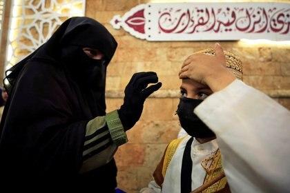 Una mujer ajusta la gorra de su hijo con una máscara facial, durante el mes de ayuno del Ramadán, en medio de la preocupación por la propagación de la enfermedad coronavirus (COVID-19), en la ciudad vieja de Sidón, en el sur del Líbano, el 19 de mayo de 2020. Foto tomada el 19 de mayo de 2020. REUTERS/Ali Hashisho