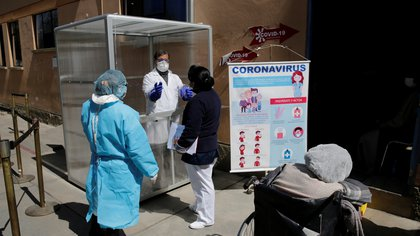 A medic shows colleagues how to use a booth to collect samples from suspected coronavirus disease (COVID-19) patients, outside the triage area of the General Hospital, in La Paz, Bolivia June 23, 2020. REUTERS/David Mercado