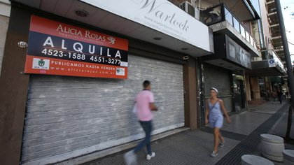 People walk past a sign of a real estate agent hanging from a closed shop, in Buenos Aires, Argentina December 12, 2018. Picture taken December 12, 2018. REUTERS/Agustin Marcarian