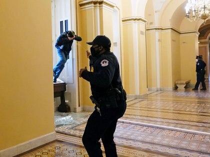 Un oficial de policía tira gas pimienta a un partidario de Trump dentro del Capitolio. Foto: Kevin Dietsch/Pool via REUTERS