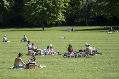 Distancia social entre quienes disfrutan de una soleada tarde en Jesus Green en Cambridge, Inglaterra.
