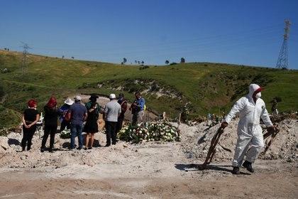 Un trabajador en traje protector camina con las correas usadas para bajar el ataúd a la tumba para el entierro de Jesús Osorio Flores, quien murió de coronavirus en el Cementerio Municipal de Tijuana No. 13, en Tijuana, México, el 24 de abril de 2020 (REUTERS/Ariana Drehsler)