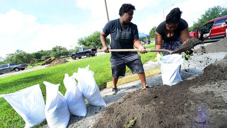 Rochelle (L) y Venicia Crise llenan bolsas de arena el 29 de agosto de 2019 en Casselberry, Florida, frente a la llegada del huracán Dorian (AFP)