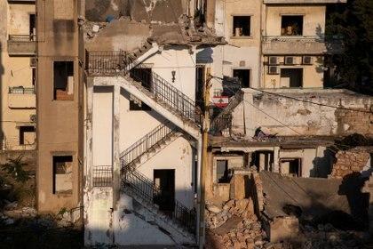 Una bandera libanesa cuelga frente a los edificios dañados por una explosión en el puerto de Beirut, en el barrio de Karantina, Líbano, el 13 de agosto de 2020. Foto: REUTERS / Alkis Konstantinidis
