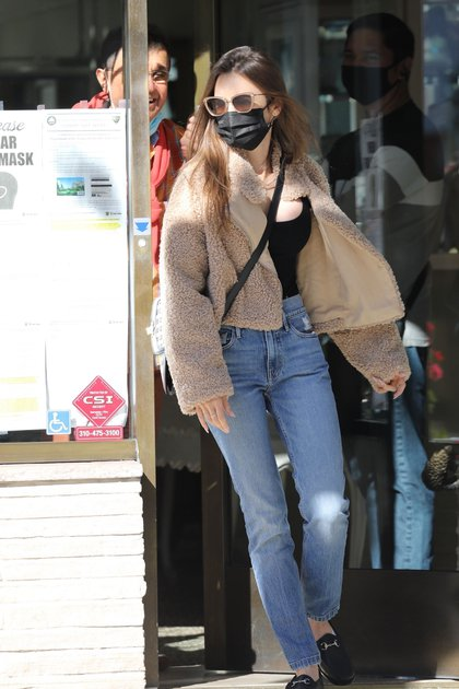 """Día de shopping. Lily Collins salió de compras por las calles de Beverly Hills, Los Ángeles, California. La actriz –popularmente conocida por su papel en """"Emily en Paris""""– lució un jean, una remera negra y una campera de peluche marrón. Además, llevó puesto su tapabocas y lentes de sol"""
