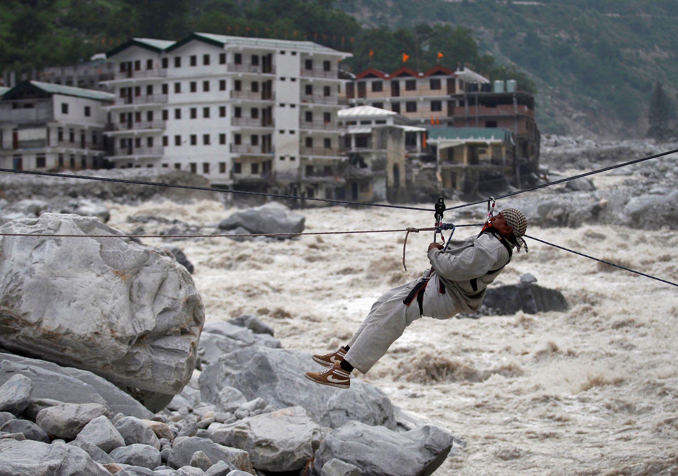 Un hombre es arrastrado a través de una cuerda para ponerse a salvo, mientras se ven los edificios dañados y el río Alaknanda en el fondo, durante una operación de rescate en Govindghat en el estado himalayo de Uttarakhand el 23 de junio de 2013.