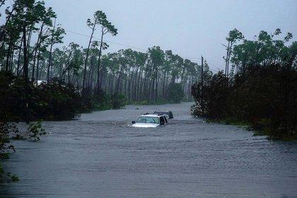 Dos automovilistas intentan pasar por calles inundadas (AP Photo/Ramon Espinosa)