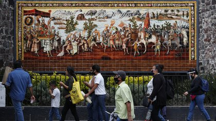 Shoppers and commuters walk along a street in central Mexico City, Monday, July 6, 2020. After three months of shutdown, officials allowed a partial reopening of the downtown commercial area last week, although COVID-19 cases continue to climb.(AP Photo/Rebecca Blackwell)