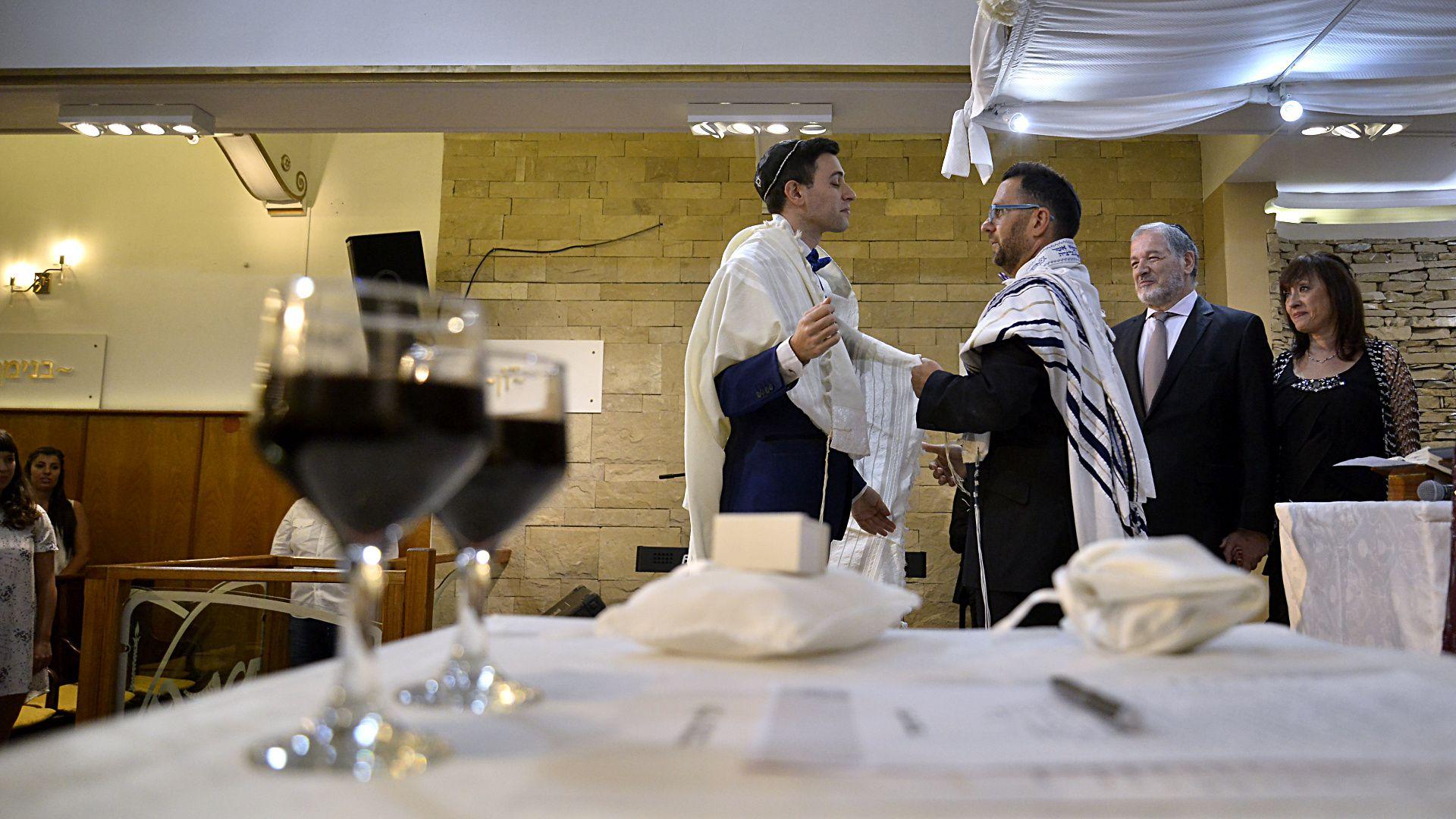 El rabino le coloca a Nicolás el talit (manto), que forma parte de uno de los momentos icónicos de la celebración judía