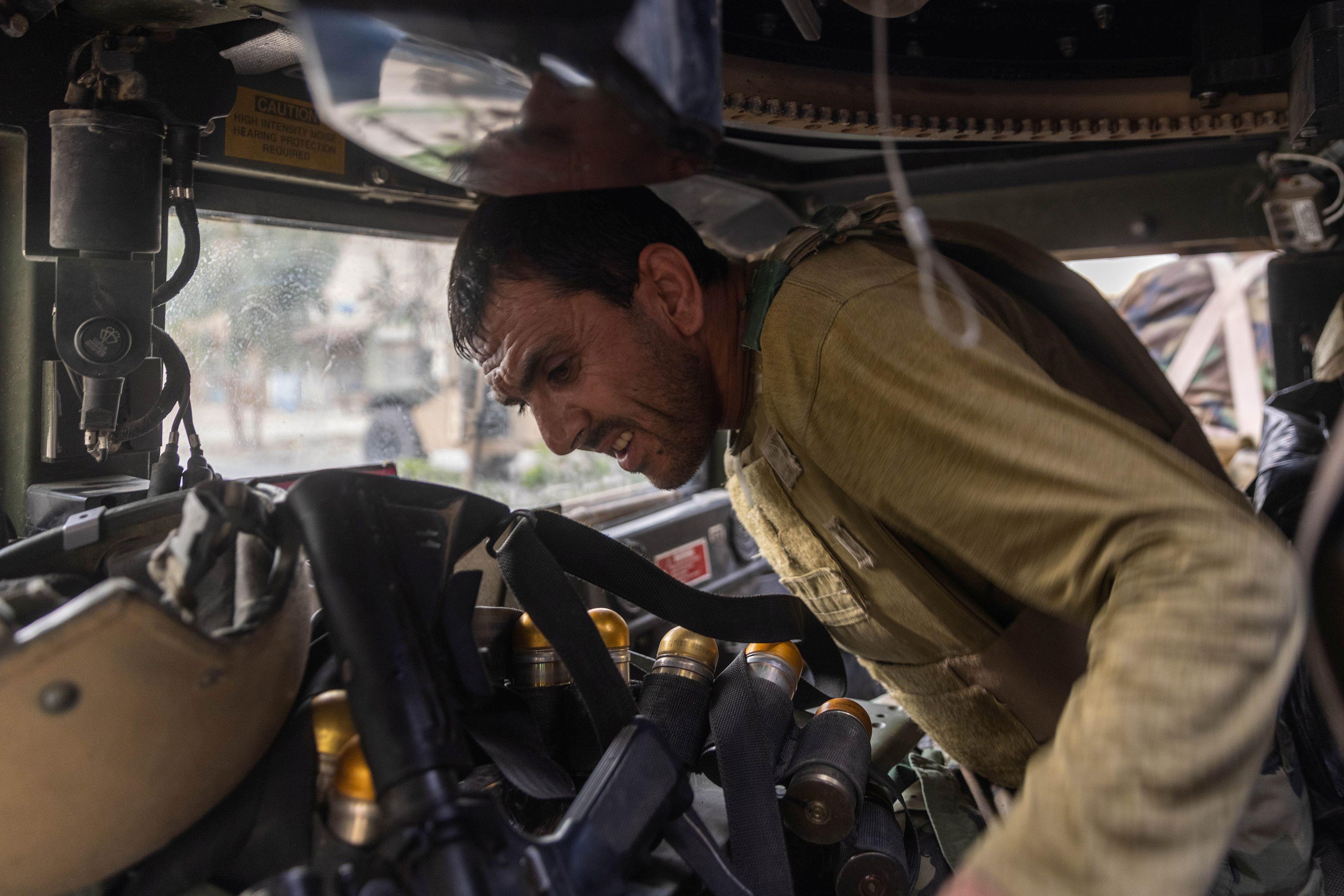 Miembros de las fuerzas especiales afganas que viajan en un humvee destruido durante los fuertes enfrentamientos con los talibanes se ponen a cubierto durante la misión de rescate de un policía asediado en un puesto de control, en la provincia de Kandahar, Afganistán, 13 de julio de 2021.