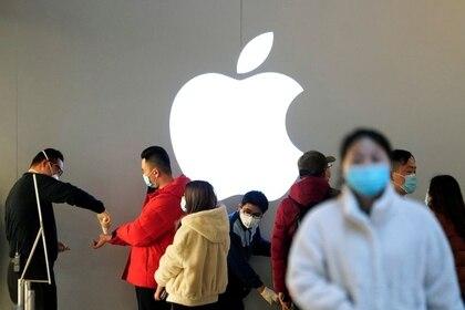 Clientes con mascarillas protectoras esperan controlar su temperatura en una tienda Apple, en Shanghai, China, mientras el país se ve afectado por un brote del nuevo coronavirus. 21 de febrero de 2020. REUTERS/Aly Song.