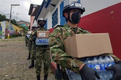Soldados del Ejército de Colombia usando tapabocas y guantes cargan cajas con alimenros y agua para entrgar a familias pobres durante la cuarentena por coronavirus en Bogotá, Colombia,  17 de abril, 2020. REUTERS/Luis Jaime Acosta