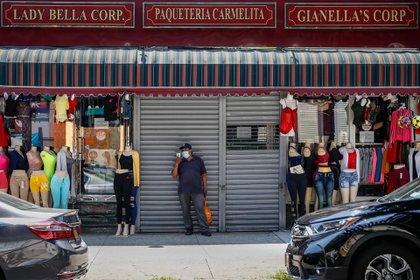 Un hombre, con mascarilla, delante de una tienda cerrada, en medio de otras dos de venta de ropa, en Queens, Nueva York. (Foto AP / John Minchillo)