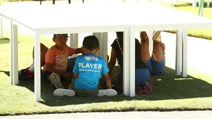 Cinco niños encontraron sombra debajo de unas mesas y allí fueron a resguardarse en medio de una jornada de intenso calor en Melbourne, Australia(Getty Images)