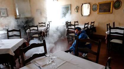 Un hombre desinfecta el restaurante Olimpo en Brescia (EFE/EPA/Filippo Venezia)