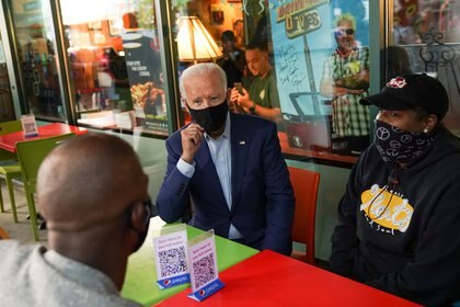 Joe Biden conversando con la estrella de la NBA Chris Paul y Tia Bazzelle, propietaria del restaurante Mert's Heart & Soul en Charlotte, Carolina del Norte, donde estaba haciendo campaña esta semana.  REUTERS / Kevin Lamarque