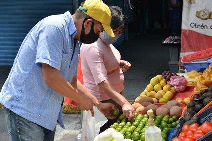 Imagen de archivo. El dueño de un puesto en un mercado al aire libre usa una máscara protectora mientras ofrece fruta a los compradores como un intento de sobrevivir al bloqueo en medio de la pandemia. México limita la venta de artículos de primera necesidad durante el brote de coronavirus en Ciudad de México, México. 8 de mayo de 2020. REUTERS/SOLO USO EDITORIAL