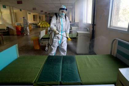 Un trabajador en traje de protección desinfecta el Hospital Wuhan No. 7, una vez designado hospital para pacientes con enfermedad por coronavirus (COVID-19), para prepararlo para la reanudación de su servicio normal en Wuhan, provincia de Hubei, China, el 19 de marzo de 2020. (Cnsphoto via REUTERS)