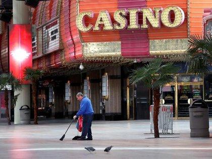 Un trabajador barre la vereda frente a un casino de Las Vegas, EEUU, cuyos negocios han quedado vacíos por las medidas para frenar la pandemia (REUTERS/Steve Marcus)