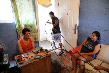 Un hombre con mangueras para el agua (REUTERS/Manaure Quintero)