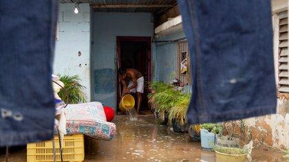 Un hombre saca agua de su casa en Maracaibo (EFE/ Henry Chirinos)