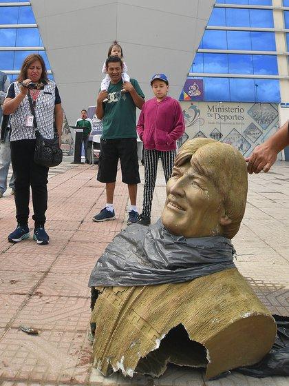Un grupo de personas toma fotografías y videos de un busto de Evo Morales que fue retirado este lunes en Quillacollo (EFE/Jorge Abrego)