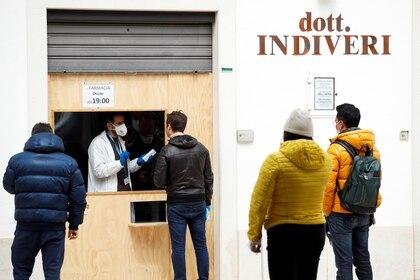 La gente hace cola frente a una farmacia en Alberobello, mientras continúa la propagación del coronavirus (COVID-19), en Italia, el 3 de abril de 2020. (REUTERS/Alessandro Garofalo)