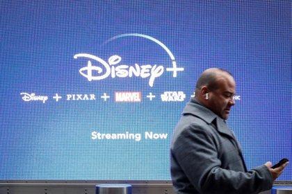 Un hombre pasa caminando frente a una pantalla promocional de Disney + (Reuters)