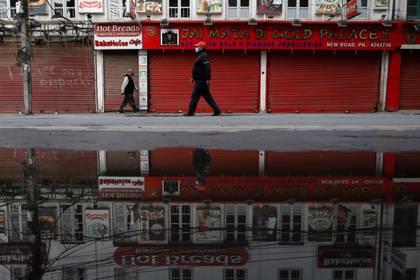 Un hombre con una máscara facial pasa frente a tiendas cerradas en medio de la preocupación por la propagación del brote del coronavirus, en Katmandú, Nepal, el 23 de marzo de 2020. REUTERS/Navesh Chitrakar