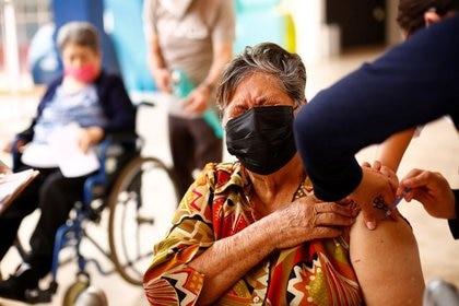 Imagen de archivo. Una anciana gesticula mientras recibe la vacuna contra la enfermedad del coronavirus de AstraZeneca (contra COVID-19), durante un programa de vacunación masiva en Ciudad Juárez, México. 12 de abril de 2021. REUTERS / José Luis González