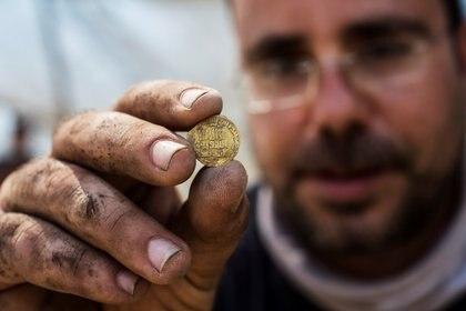 Shahar Krispin uno de los  arqueólogos israelíes que participaron de la investigación, muestra una de las moneda de oro (Reuters)