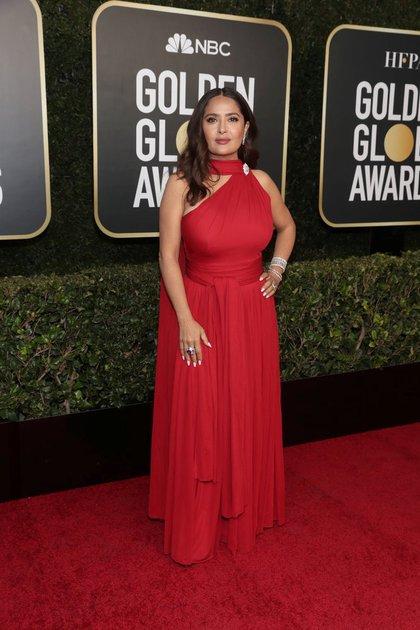 La actriz mexicana Salma Hayek lució un vestido color rojo de cuello halter con falda de diseño en cascada. Completó el look con anillos, brazaletes y de diamantes de Harry Winston