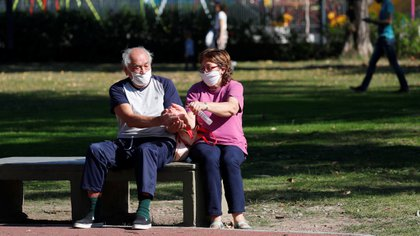 Una pareja se desinfecta en un banco de una plaza en Buenos Aires en medio de la pandemia por COVID-19 - REUTERS/Agustin Marcarian