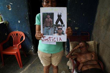 Judith Cortez sostiene fotos de sus hijos José Alfredo y Anderson Torres, fusilados por miembros de la Fuerza de Acción Especial de la Policía Nacional Venezolana (FAES).