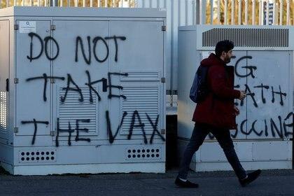 File foto: una persona passa graffiti anti-vaccino tra lo scoppio della malattia da virus corona (COVID-19) il 1 ° gennaio 2021 a Belfast, nell'Irlanda del Nord.  REUTERS / Bill Noble