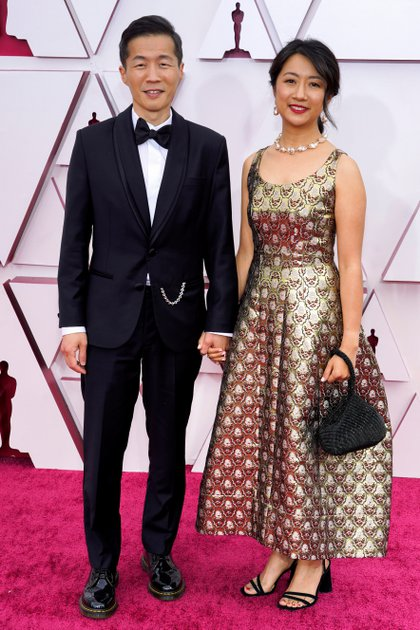 Lee Isaac Chung con un impecable black tie asistió a la ceremonia de los Oscar 2021 con Valerie Chung, quien lució un vestido al tobillo con breteles gruesos, mini bag y zapatos negros de taco cuadrado